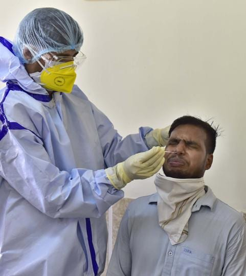 A health worker in PPE coveralls collecting swab sample of a Ludhiana Improvement Trust employee.