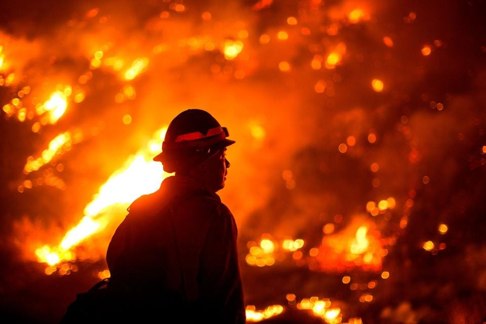 TOPSHOT - A firefighter watches the Bobcat Fire burning on hillsides near Monrovia Canyon Park in Monrovia, California on September 15, 2020. - A major fire that has been raging outside Los Angeles for more than a week threatened to engulf a historic observatory and billion-dollar broadcast towers on September 15 as firefighters struggled to contain the flames. The so-called Bobcat Fire was within 500 feet (150 meters) from the 116-year-old Mt. Wilson Observatory, the US Forest Service said in a tweet, while fire officials said crews were in place