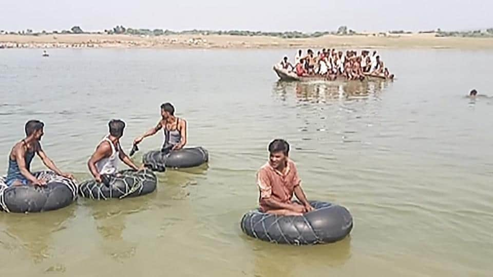 Rescue teams carry out search operations for missing people after a boat sank while crossing Chambal River.