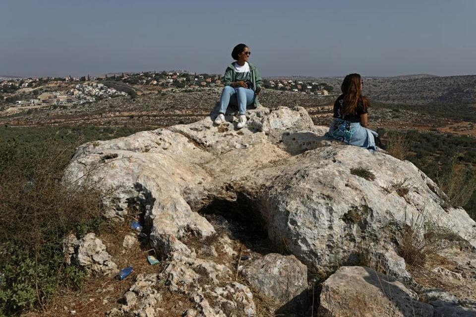 Young Palestinian travel bloggers Malak Hasan and Bisan Alhajhasan sit at the remains of an archeological site in the village of Aboud near Ramallah in the Israeli-occupied West Bank September 15, 2020.  (REUTERS)