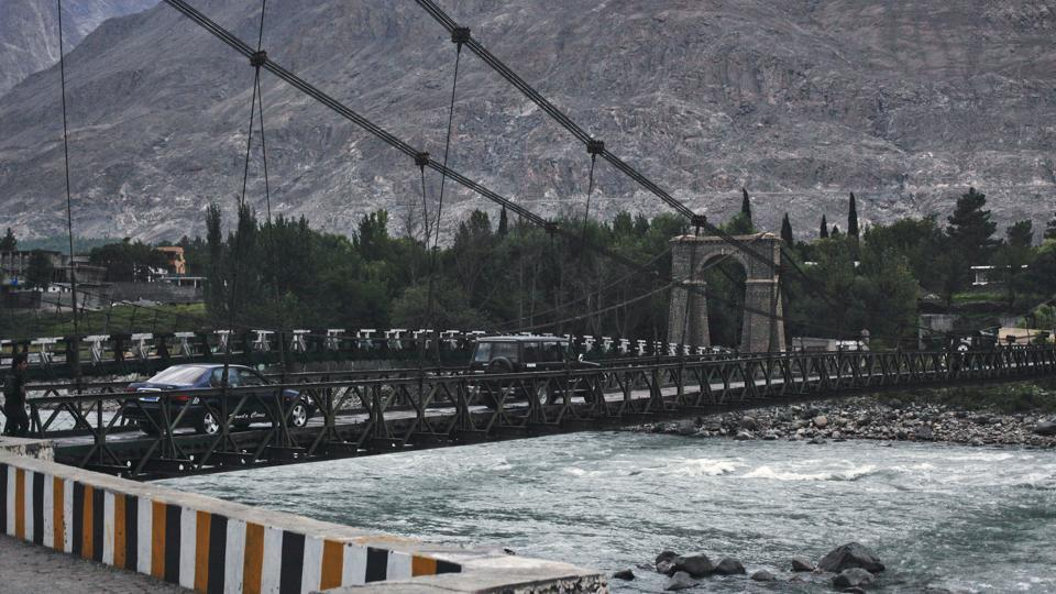 Vehicles cross a wooden plank cable suspension bridge over the Indus river in Gilgit.