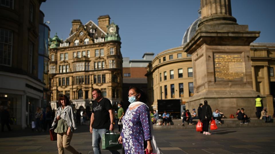 Pedestrians and shoppers, some wearing a face mask or coverings due to Covid-19, walk in Newcastle city centre, north-east England, on September 17.