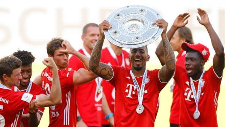 Bayern Munich's Jerome Boateng, Thomas Muller, Kingsley Coman, Leon Goretzka and Alphonso Davies celebrate with the trophy after winning the Bundesliga.
