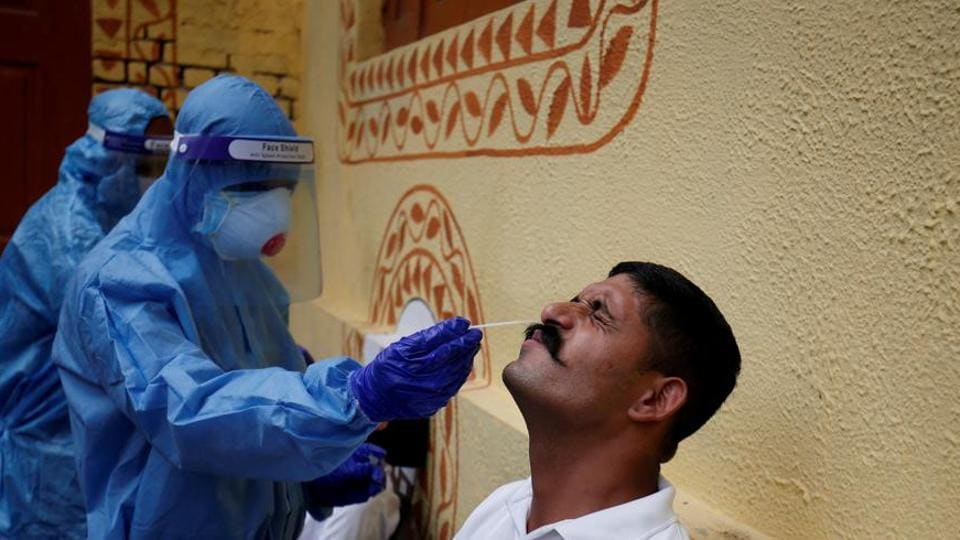 A healthcare worker wearing personal protective equipment (PPE) takes a swab from a police officer for a rapid antigen test.