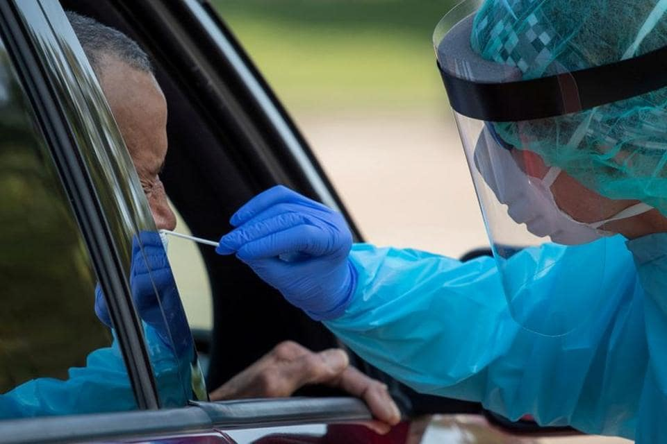 FILE PHOTO: A healthcare worker uses a swab to test a man at a coronavirus disease (Covid-19) drive-in testing location in Houston, Texas, US (REUTERS/Adrees Latif/File Photo)