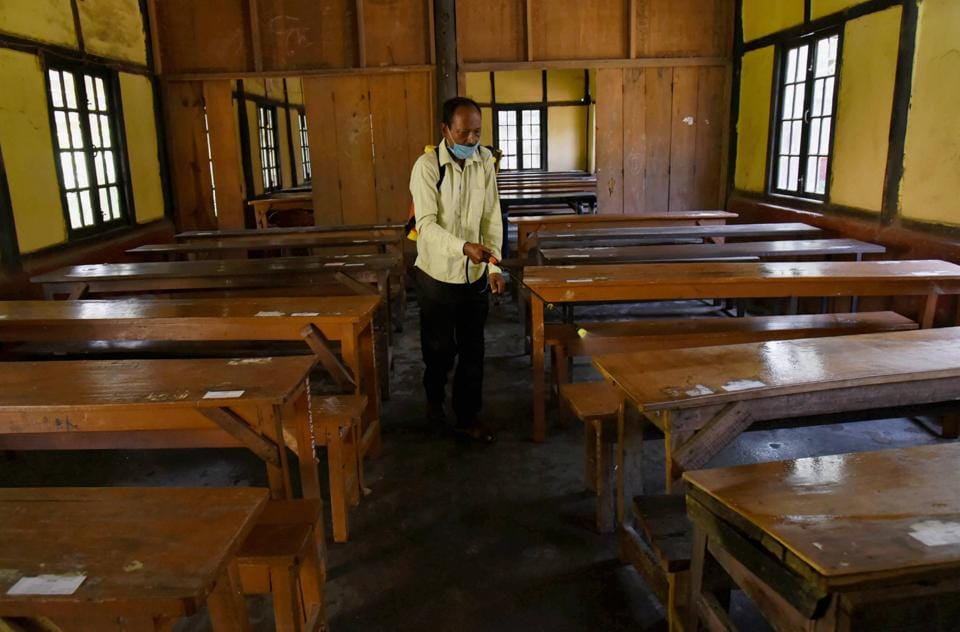 Guwahati: A staff member sprays disinfectant on benches ahead of the reopening of schools from September 21, during Unlock 4.0, at Sonaram Higher Secondary School in Guwahati, Friday.