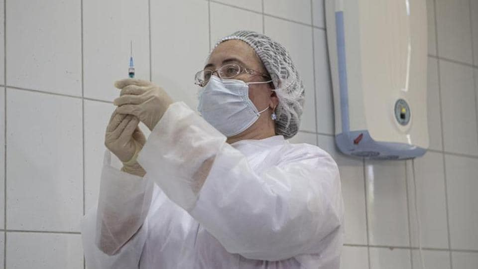 A Russian medical worker prepares a shot of Russia's experimental Sputnik V coronavirus vaccine for its use in Moscow.  Mikhail Murashko, the Russian health minister, said more than 300 out of the announced 40,000 volunteers have been vaccinated with Sputnik V so far.