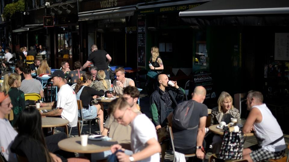 Members of the public sit on a terrace as they enjoy the weather in central London.