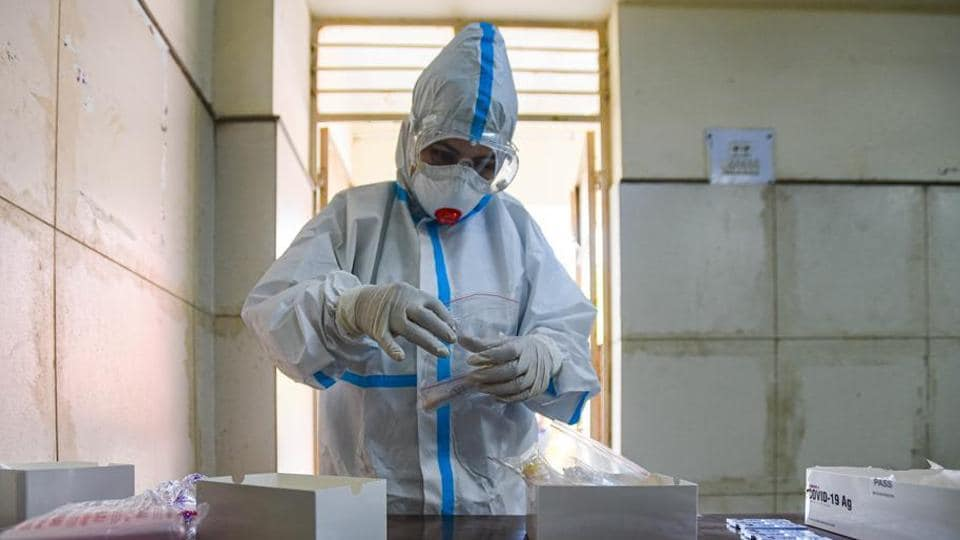 A health worker in PPE coveralls gets ready to collect swab samples for coronavirus testing.