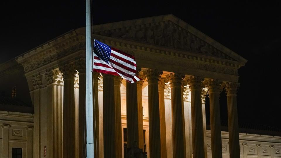 The American flag blows in the wind after it was lowered to half-staff Friday, Sept. 18, 2020, in Washington, after the Supreme Court announced that Supreme Court Justice Ruth Bader Ginsburg has died of metastatic pancreatic cancer at age 87.