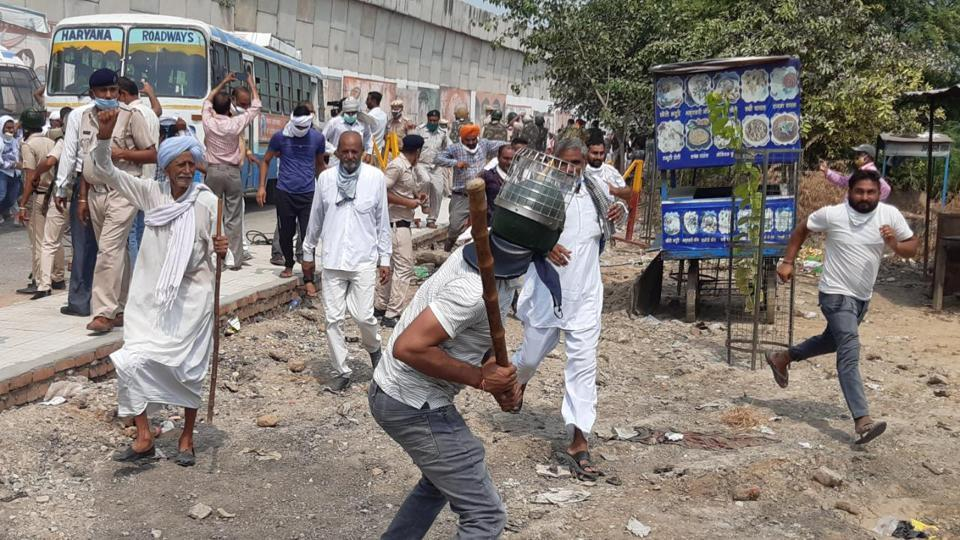 A plainclothes police personnel swings a lathi as members of Bhartiya Kisan Union block National Highway-44 near Kurukshetra after a proposed protest rally of farmers and commission agents was foiled by heavy police presence, Haryana, September 10, 2020.