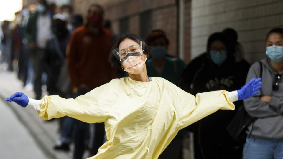 A health care worker poses for a photograph while walking towards a line of patients waiting outside a Covid-19 testing center at St. Michael's Hospital in Toronto, Ontario, Canada, on Sept. 18.