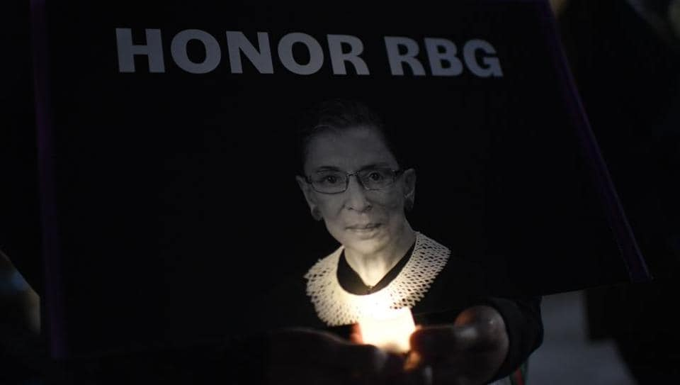 A woman holds a candle as people pay their respects to Ruth Bader Ginsburg near the US Supreme Court in Washington, DC on September 19.