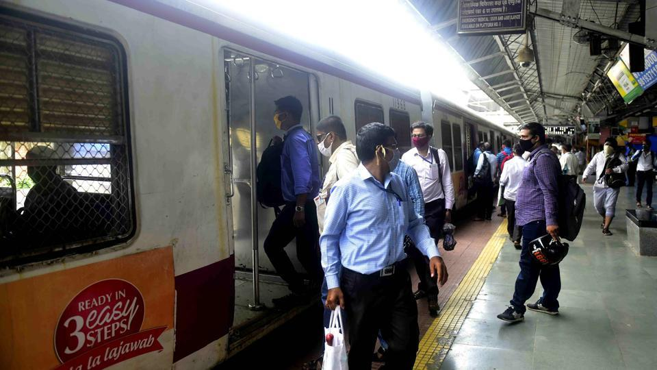 Workers of essential services board the local train at Dadar in Mumbai.