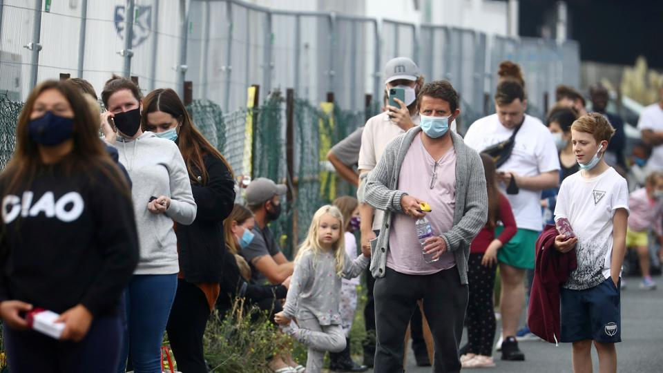 People queue at a test centre following an outbreak of the coronavirus disease in Southend-on-sea, Britain.