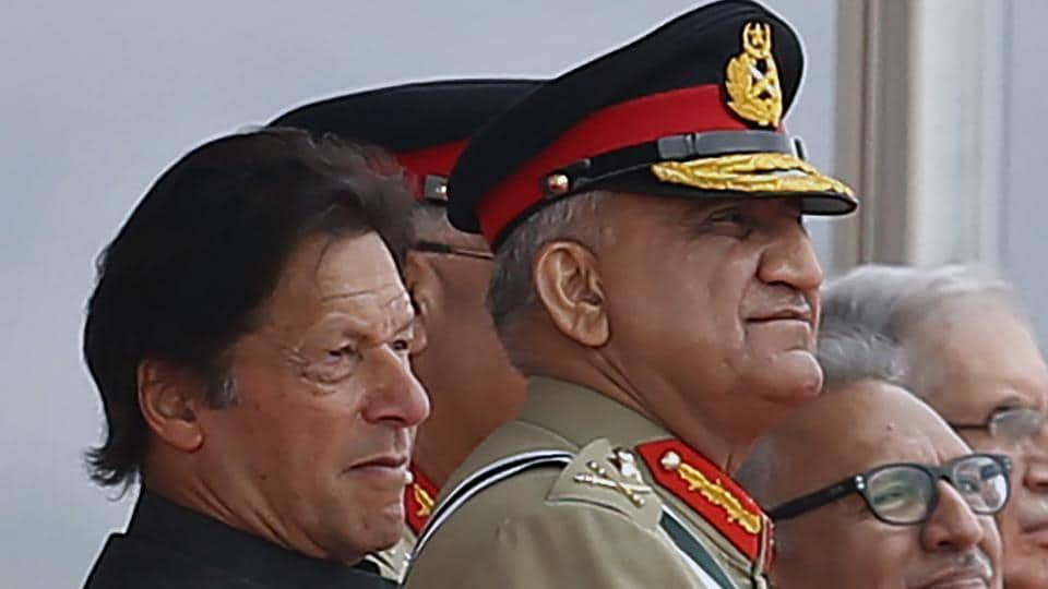 Pakistan's Army Chief Gen. Qamar Javed Bajwa, center, watches a parade with Pakistan Prime Minister Imran Khan.