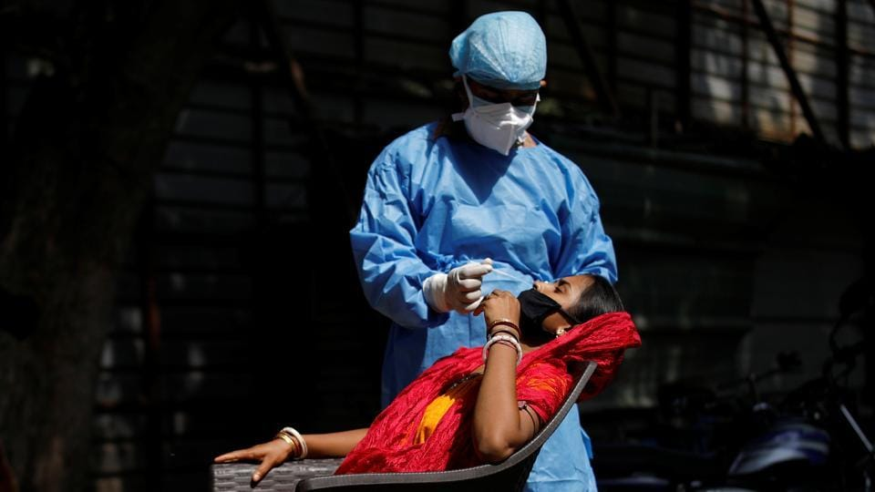 A health worker takes a swab of a woman to test for the coronavirus disease in this file photo. Data showed India recorded 92,605 new infections and 1,333 patients died between Saturday and Sunday morning.