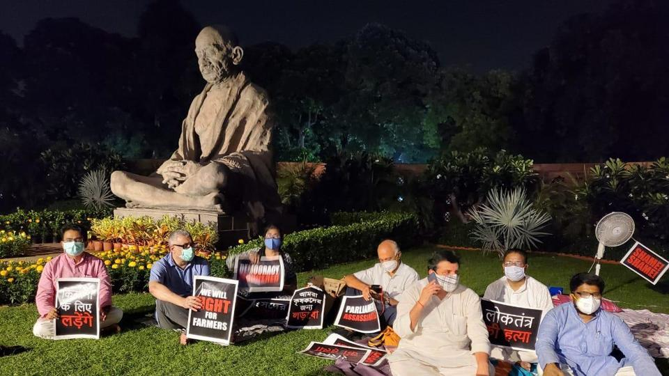 The suspended members of Rajya Sabha sit near the Gandhi statue in Parliament on Monday evening.