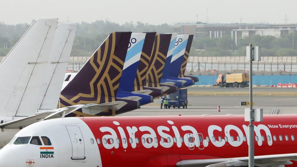 Aircraft operated by AirAsia Bhd, Vistara, a joint venture between Singapore Airlines and Tata Group, and IndiGo, a unit of InterGlobe Aviation Ltd., stand at Terminal 3 of Indira Gandhi International Airport in New Delhi.