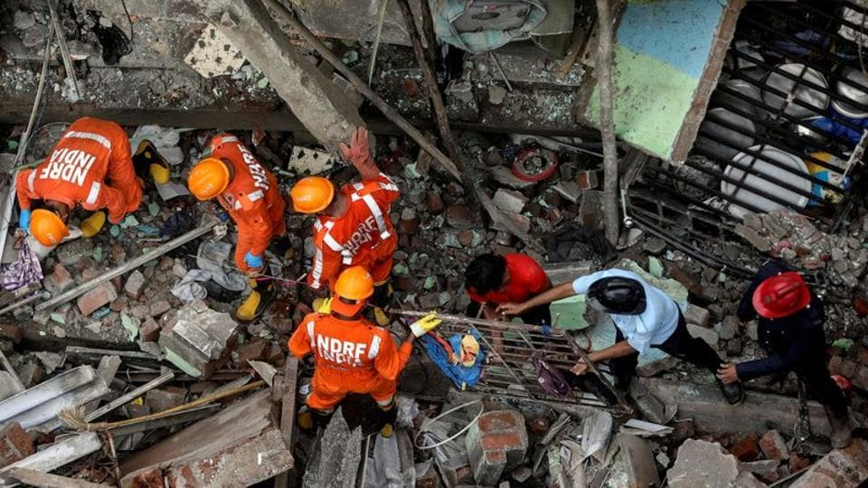 National Disaster Response Force officials and firemen remove debris as they look for survivors after a three-storey residential building collapsed in Bhiwandi on the outskirts of Mumbai on September 21.