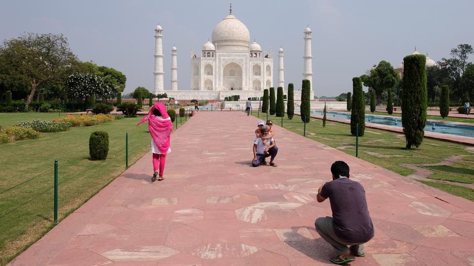 A man gets his photograph taken in front of Taj Mahal