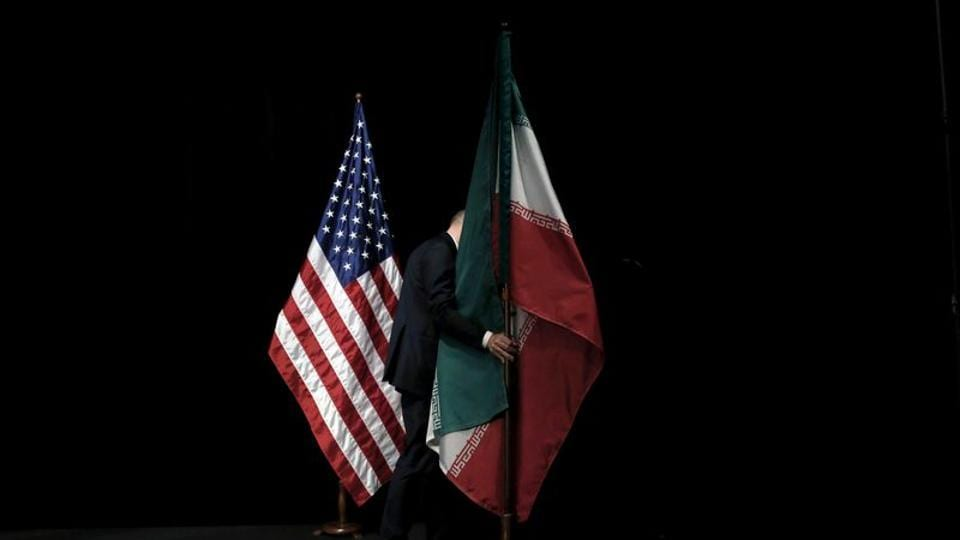 A staff member removes the Iranian flag from the stage after Iran nuclear talks at the Vienna International Center in Vienna, Austria on July 14, 2015.