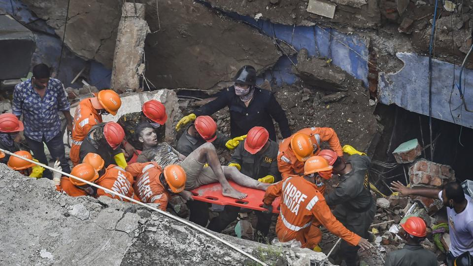 National Disaster Response Force (NDRF) and fire brigade rescue an injured person in Bhiwandi.