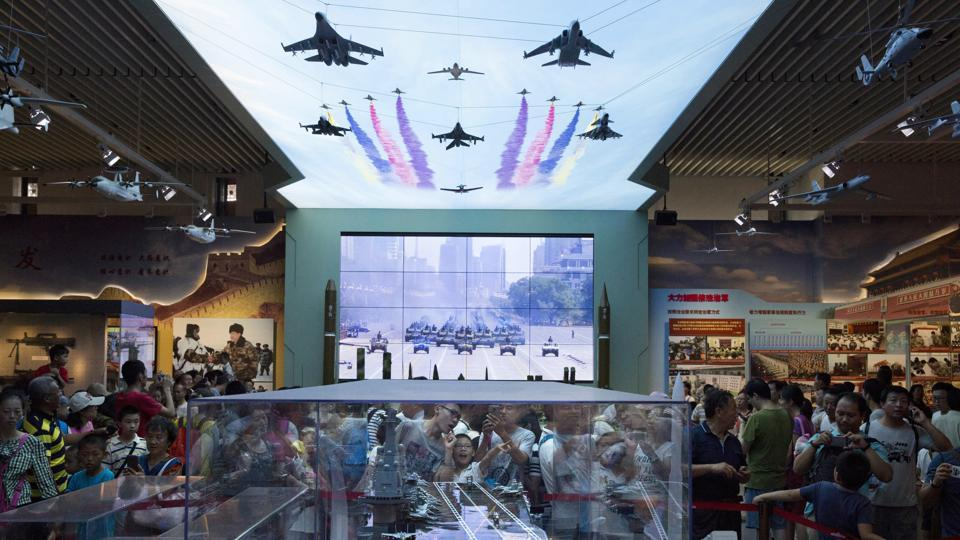 Chinese Air Force received flak in social media for using clips from Hollywood movies in the promotional video for the Chinese Air Force. In this file photo, visitors look at a scale model of a Chinese aircraft carrier during an exhibition to mark the 90th anniversary of the founding of the People's Liberation Army at the military museum in Beijing.