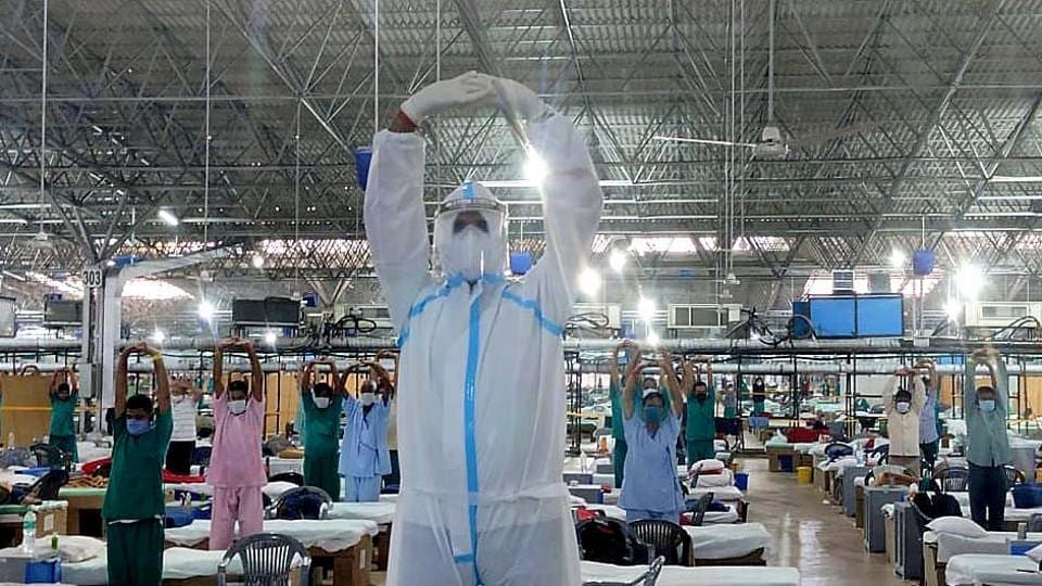 A medical professional in PPE coveralls leads patients during a yoga session at Sardar Patel Covid-19 Care Centre and Hospital in Chhatarpur, New Delhi on September 21. The number of cases for coronavirus disease (Covid-19) has seen a fall in Delhi and Mumbai, the two largest cities in the country, are also among its worst Covid-19 hit regions, HT reported. (HTPhoto)