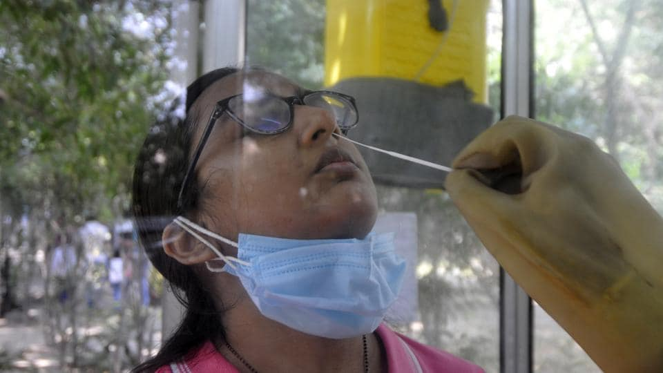 A health worker collects a swab sample from a woman for coronavirus tests, at Sector 30 District Hospital, in Noida.