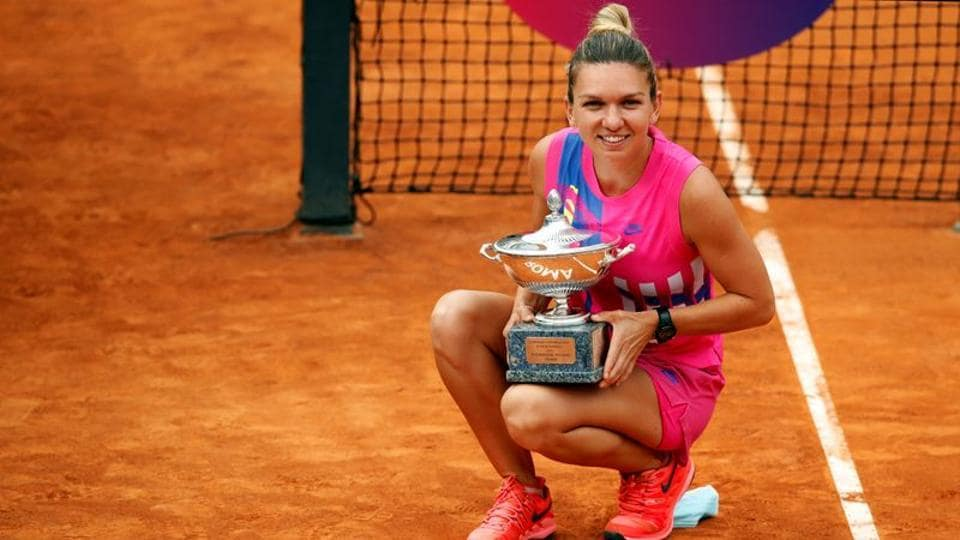 Romania's Simona Halep as she celebrates winning the final with the trophy after Czech Republic's Karolina Pliskova retired from the match after sustaining an injury.
