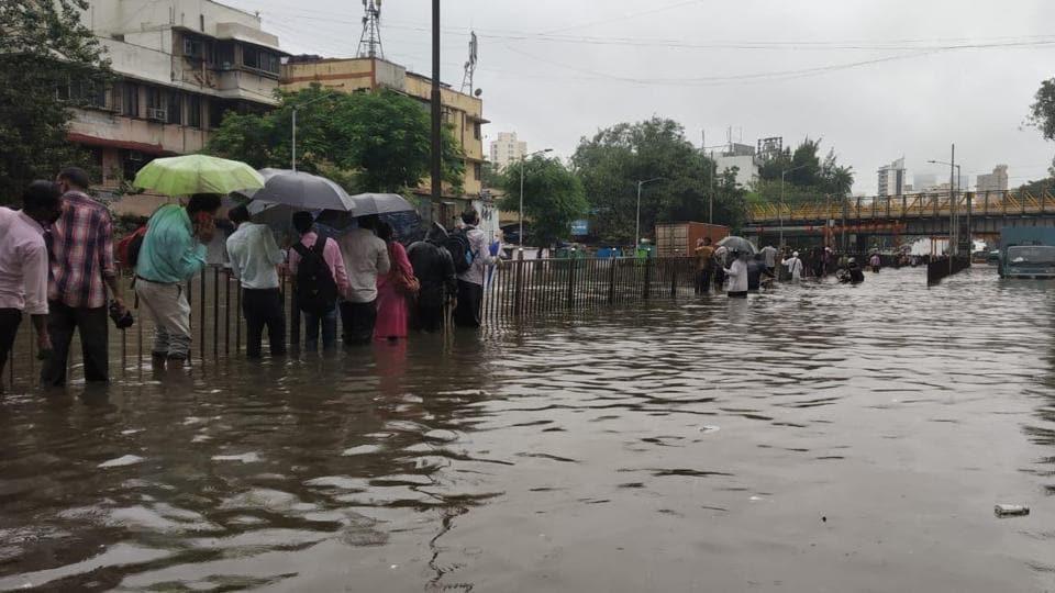 Pedestrians try to reach their destinations amid heavy waterlogging.