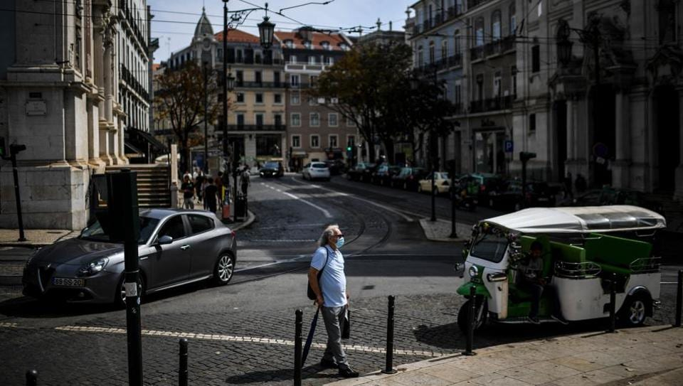 A man wearing a face mask crosses a street in Lisbon on September 22, 2020.