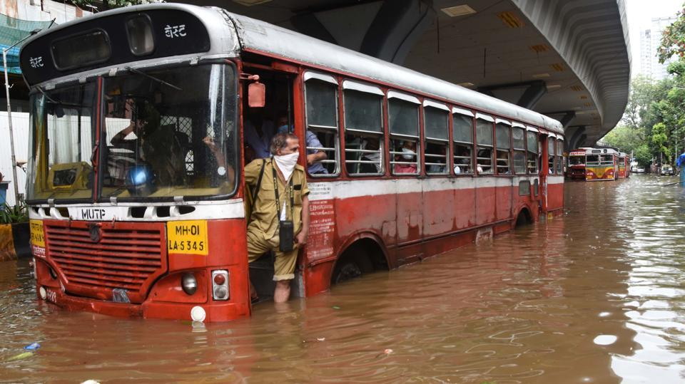 A Brihanmumbai Electricity Supply and Transport (BEST) conductor looks out from a bus stuck in a waterlogged stretch at Lalbaug in Mumbai on September 23. Mumbai's suburbs witnessed an incessant downpour between September 22 evening and September 23 morning. This is the heaviest rain the suburbs have received this season and the second-highest 24-hour September spell in 26 years (1994-2020), HT reported. (Bhushan Koyande / HT Photo)