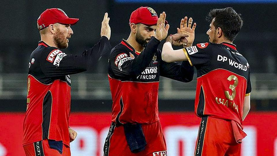 Royal Challengers Bangalore players Yuzvendra Chahal, Virat Kholi and others celebrate the wicket of Sunrisers Hyderabad batsman Manish Pandey during a cricket match of IPL 2020.