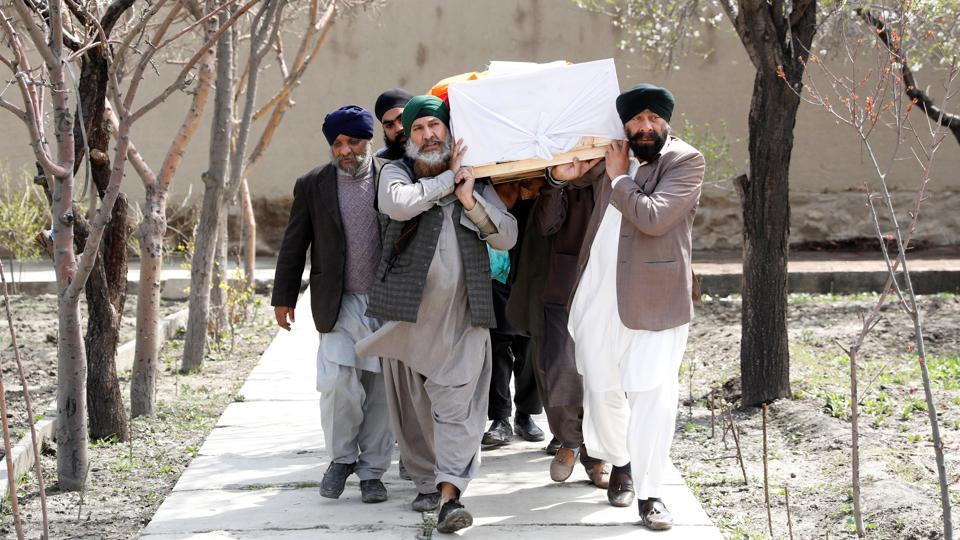 Afghan Sikh men carry a coffin of one of the victims who was killed in an attack on a gurdwara  in Kabul in  March 26.