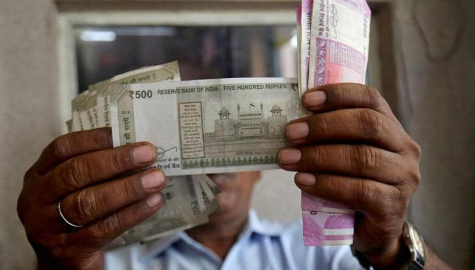 A cashier checks Indian rupee notes inside a room at a fuel station in Ahmedabad (REUTERS/Amit Dave/Files)
