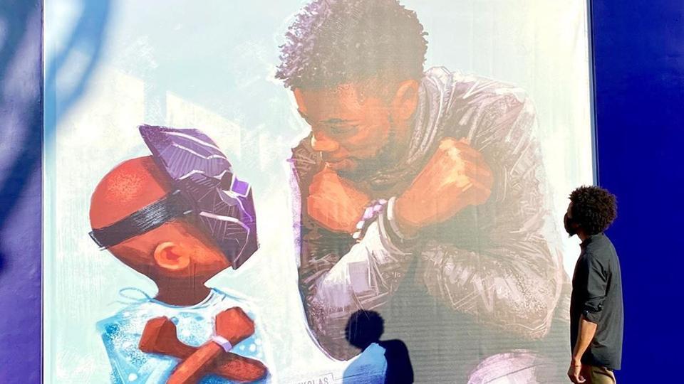 Nikkolas Smith stands next to his tribute for Chadwick Boseman at Disneyland California.