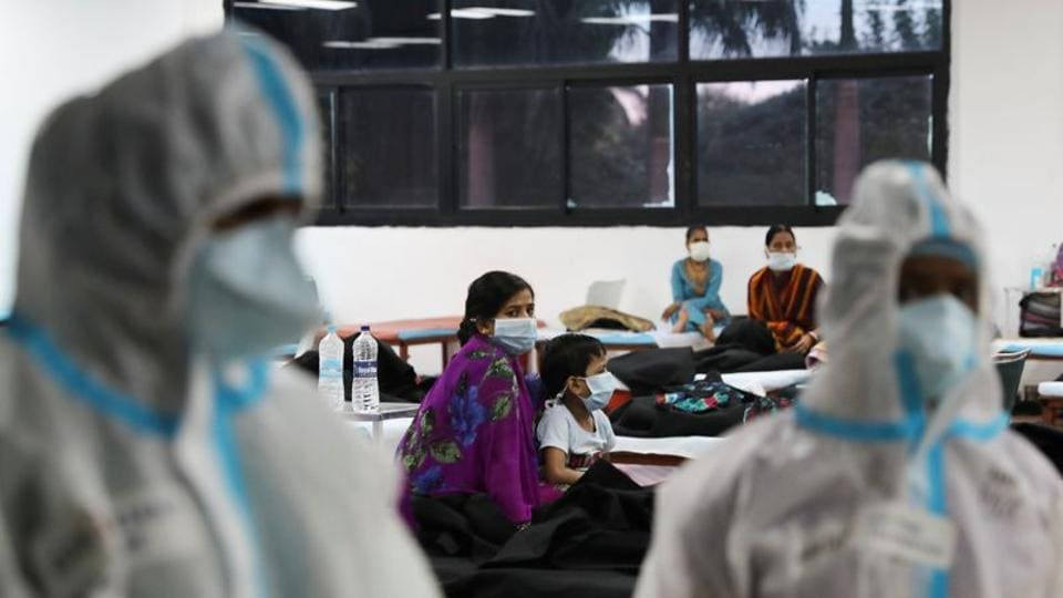 A woman sits with her child inside a quarantine centre for the coronavirus disease patients amidst the spread of the disease at an indoor sports complex in New Delhi, India.