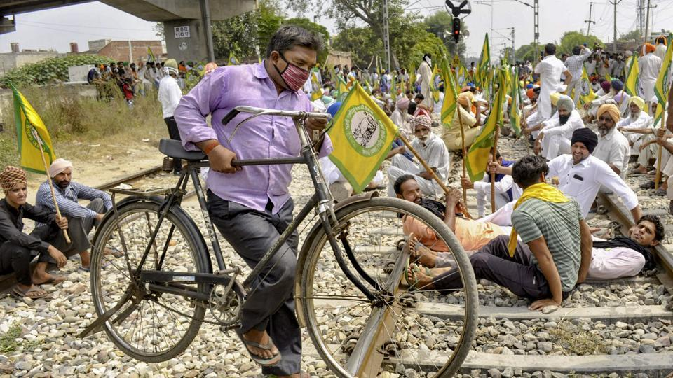 Members of various farmer organizations block a railway track during a protest.
