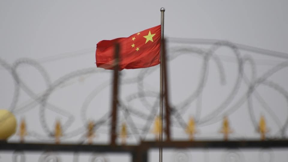 Chinese flag behind razor wire at a housing compound in Yangisar, south of Kashgar, in China's western Xinjiang region.
