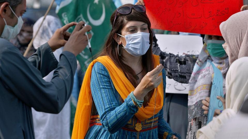 In this September 11, 2020 photo, Mona Khan, a freelance journalist, interviews during a rally in Islamabad, Pakistan. In recent weeks, social media attacks against Pakistan's women journalists have been vile, prompting the Committee to Protect Journalists to issue a statement on September 18, condemning the relentless attacks.