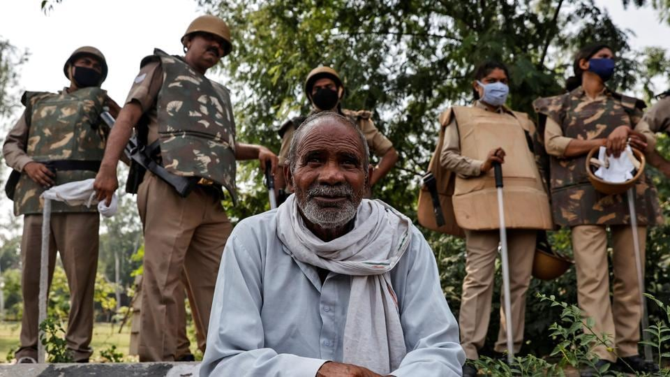 A farmer rests as police officers stand guard during a protest against farm bills passed by parliament, at the Delhi-Uttar Pradesh border, in New Delhi, September 25, 2020.
