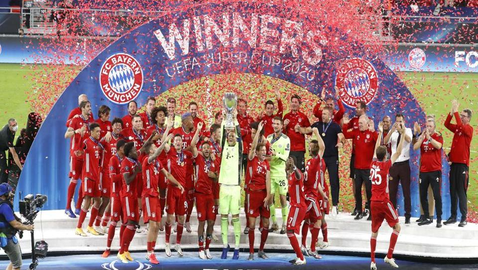 Bayern's goalkeeper Manuel Neuer holds the trophy as team mates celebrate after the UEFA Super Cup soccer match between Bayern Munich and Sevilla at the Puskas Arena in Budapest, Hungary.