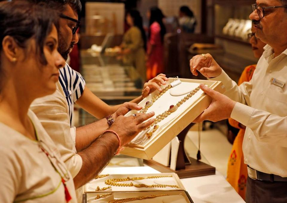 A salesman shows a gold necklace to customers at a jewellery showroom in Ahmedabad in this file photo.
