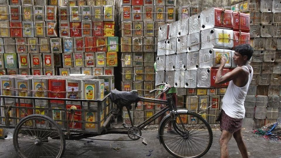 A man loads empty containers of edible oil onto a tricycle at a roadside in Kolkata, India.