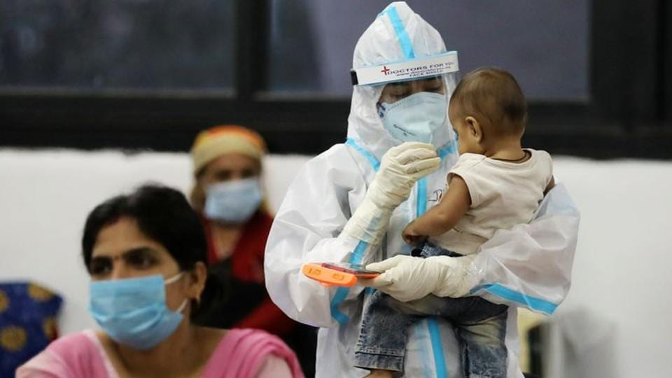 A medical worker in personal protective equipment (PPE) plays with a child of woman recovering inside a quarantine centre for the coronavirus disease (COVID-19)  in New Delhi.