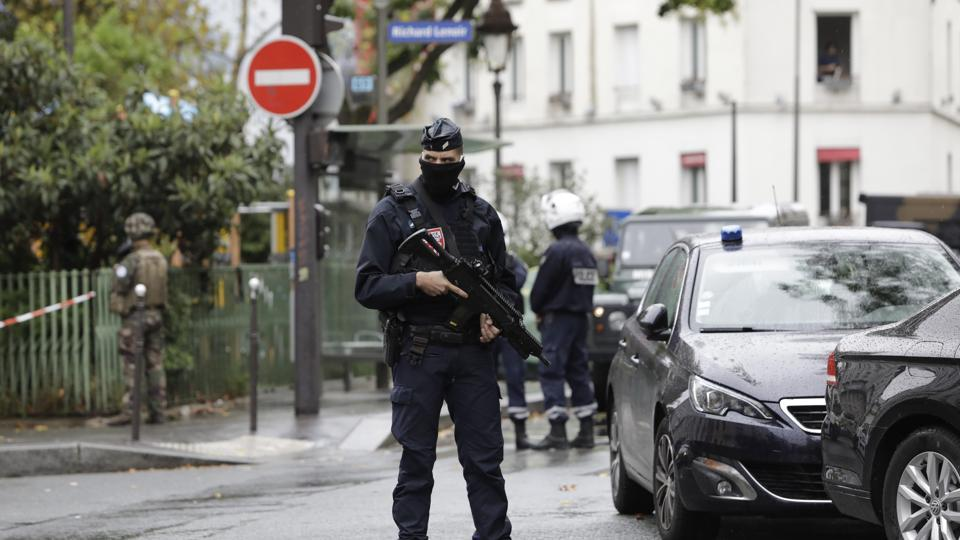 A French riot police officer stands guard after a knife attack near the former offices of satirical newspaper Charlie Hebdo, Friday Sept. 25, 2020 in Paris.