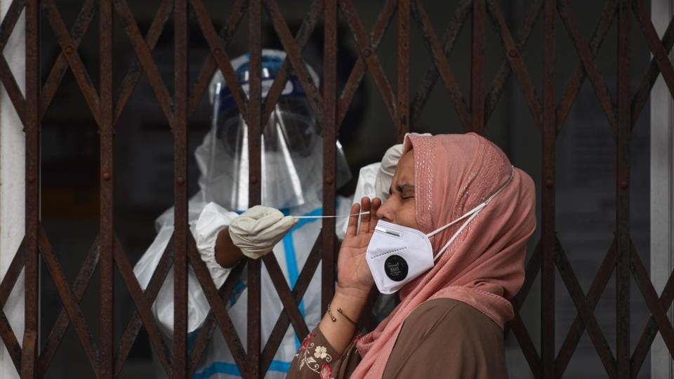 A health worker collects a swab sample for coronavirus testing at Sukhdev Vihar in New Delhi on Saturday.