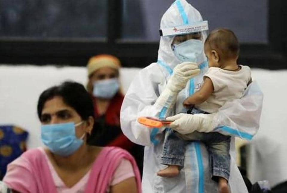 A medical worker in personal protective equipment (PPE) plays with a child of woman recovering inside a quarantine centre for the coronavirus disease (Covid-19) patients in New Delhi in this file photo.